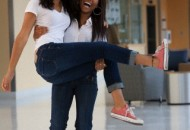 Female student carrying her friend at school and smiling